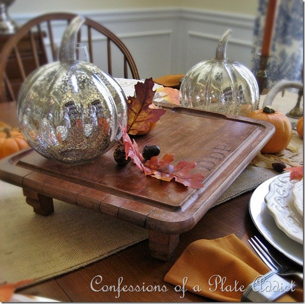 This monogrammed serving board decorated with silver pumpkins and fall leaves is rustic for fall.