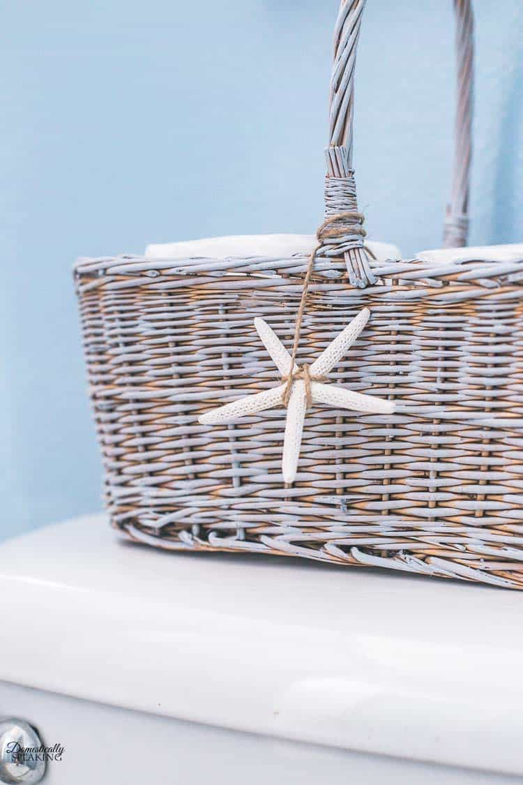 This painted vintage basket with a seashell is a fun coastal design element for the bathroom.
