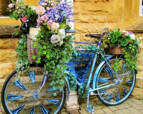 This vintage blue bike with fresh flowers throughout is colorful and fun.