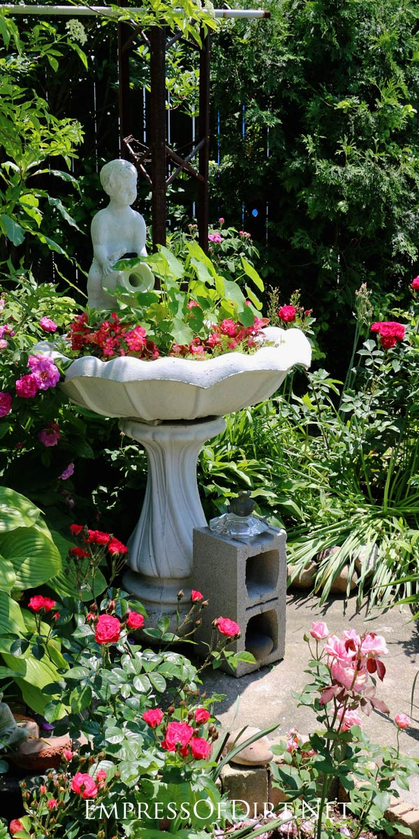 This vintage bird bath with fresh pink flowers is charming in the garden.