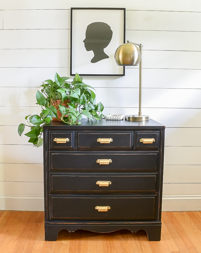 this farmhouse style scene is complete with a vintage dresser, silhouette art, and a modern gold lamp