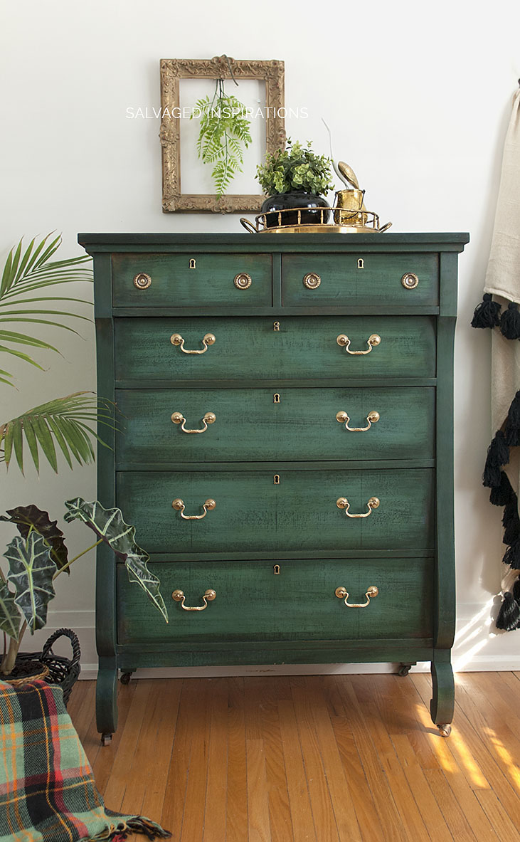 This dark green dresser with gold hardware is unique and adds color to the space.