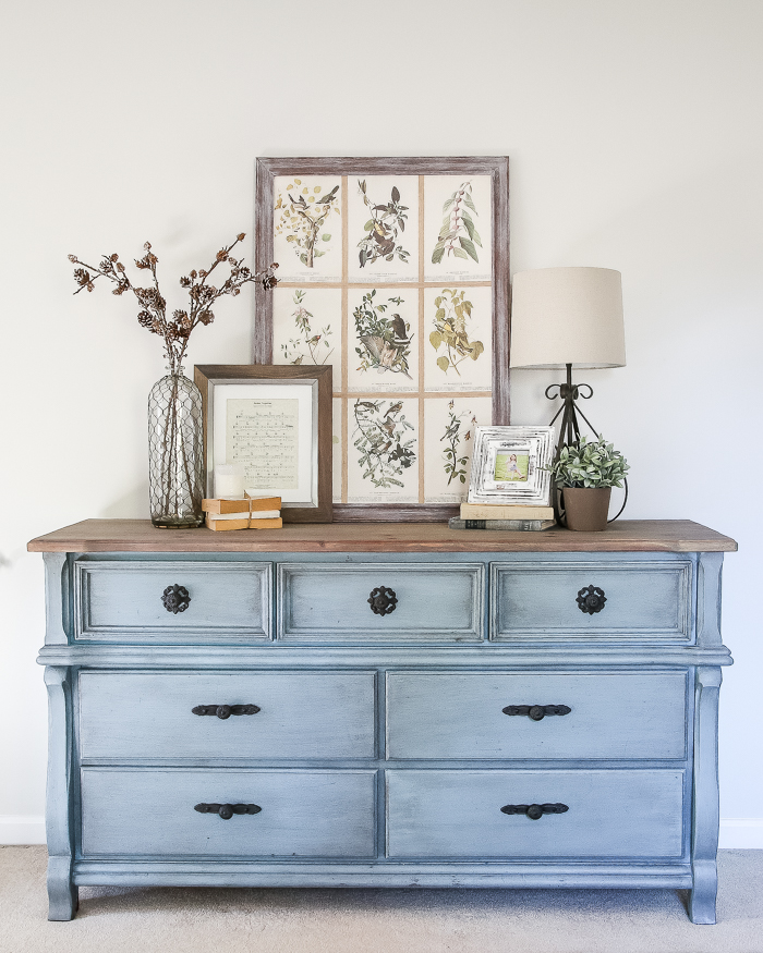 This vintage dresser painted blue with dark hardware and a wooden top is farmhouse and chic.