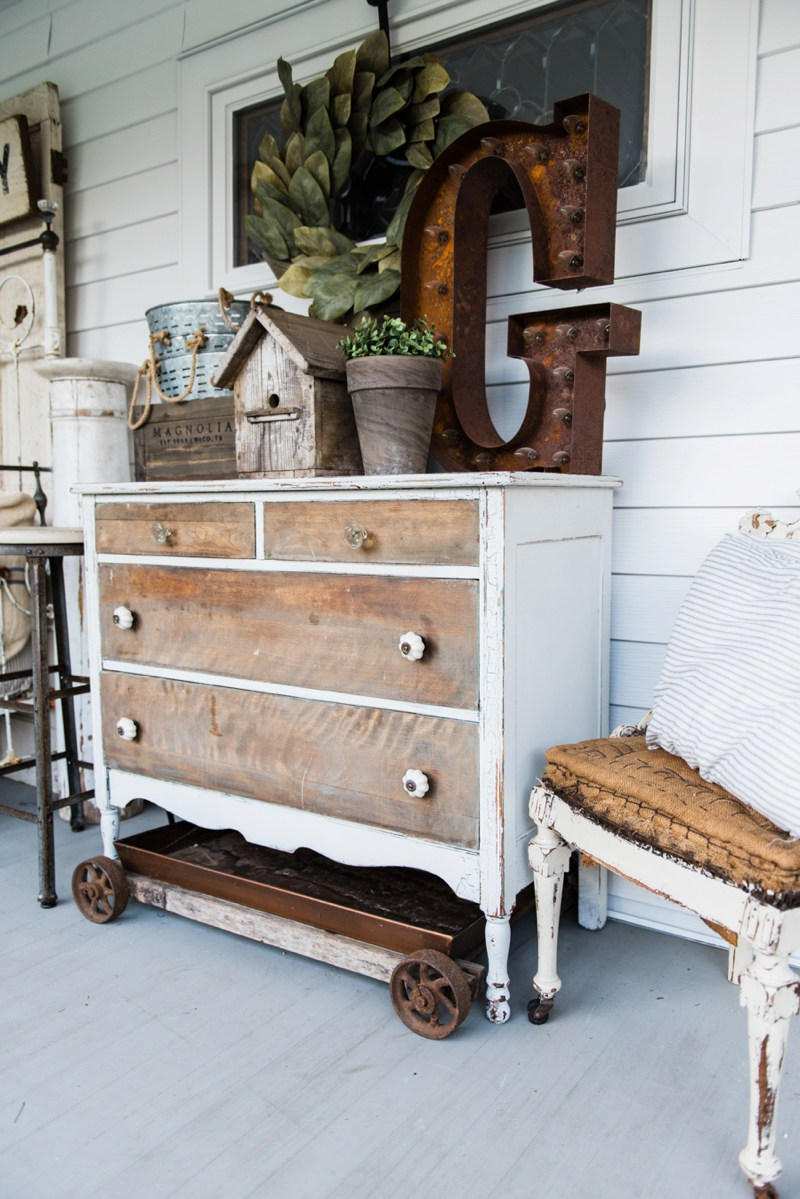This rustic dresser with distressed wood pairs well with the vintage accessories on top.