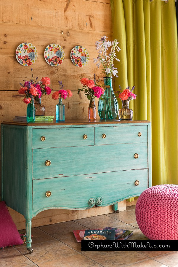 This bright turquoise dresser is color full and compliments the pink floral decor.
