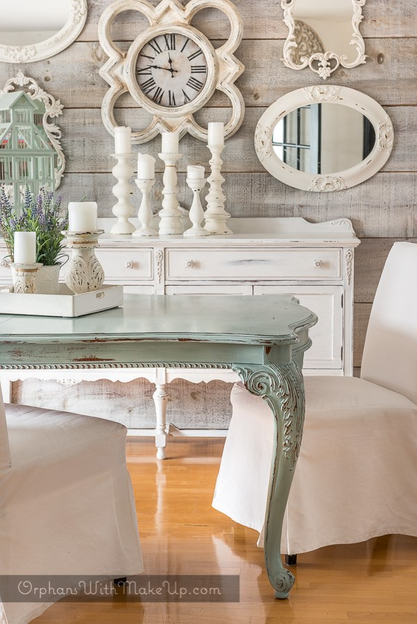 The white vintage dresser in this dining room compliments the hardwood floors.