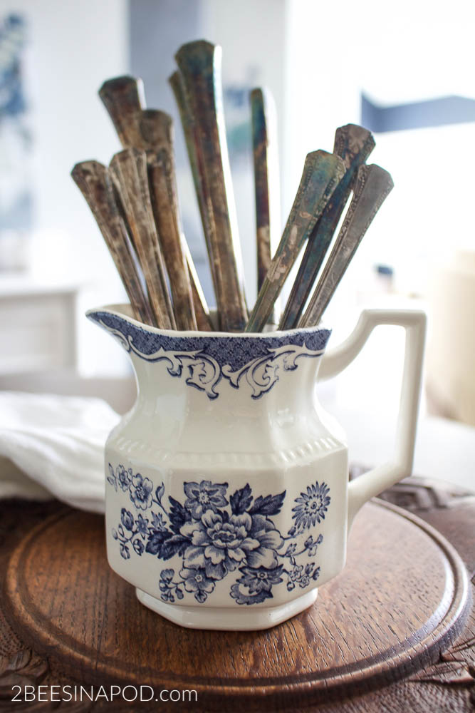 This small creamer jar and vintage silverware is likely to be found at antique shops