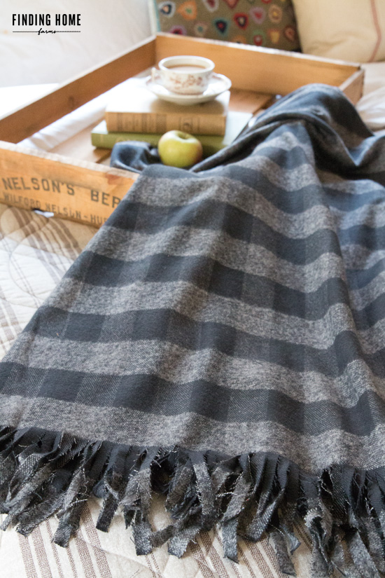 This cozy patched blanket pairs well with the wooden table tray.