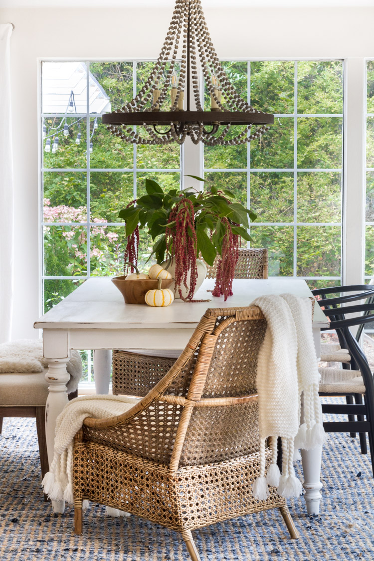 This farmhouse style dining room looks great with the touches of wicker, greens, and that gorgeous chandelier