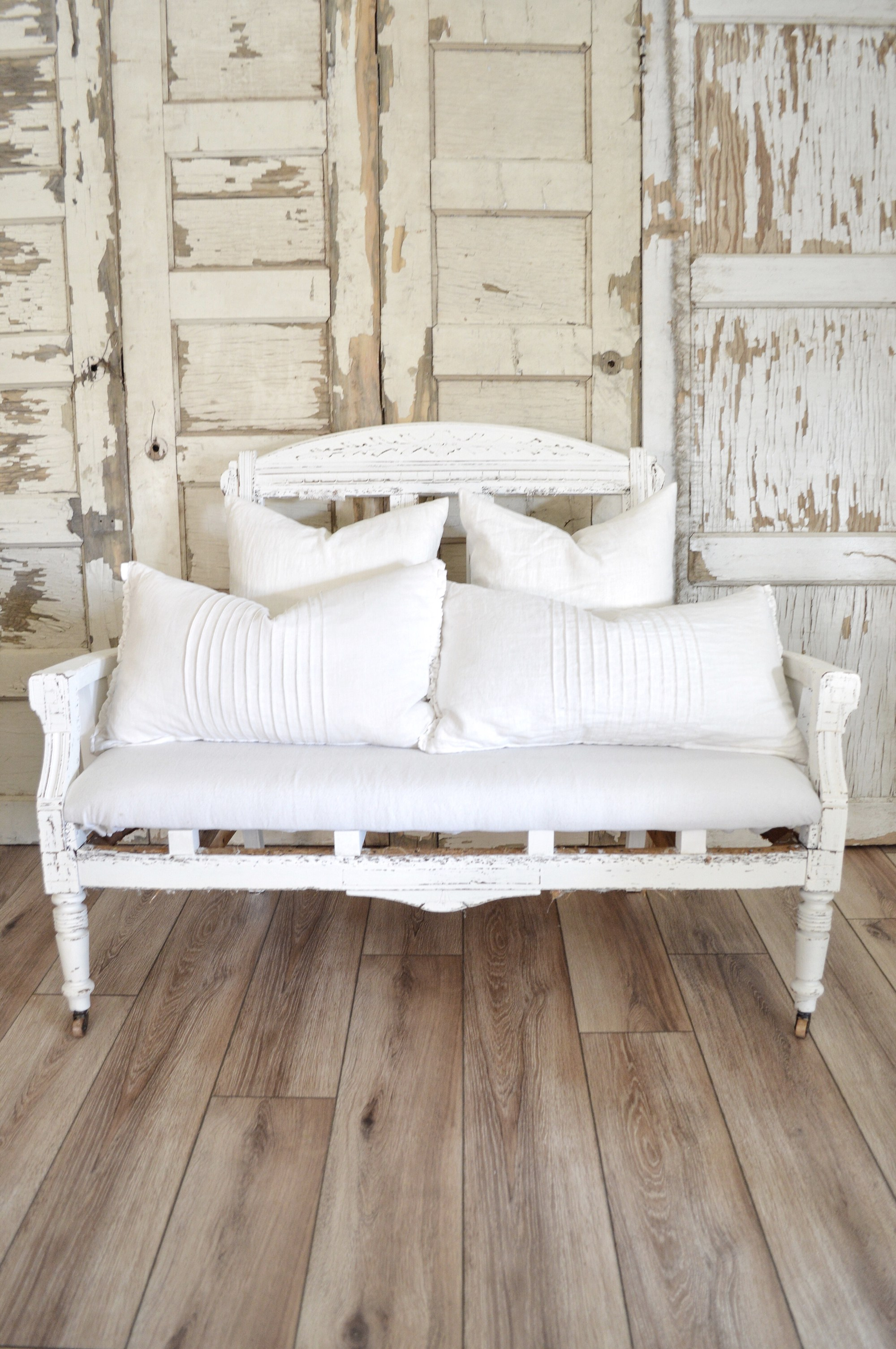 This incredible farmhouse style porch is complete with this white Settee bench