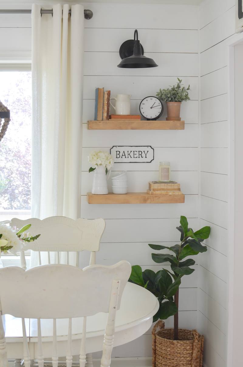 Simple farmhouse touches like these floating shelves, plants and signs are all you need