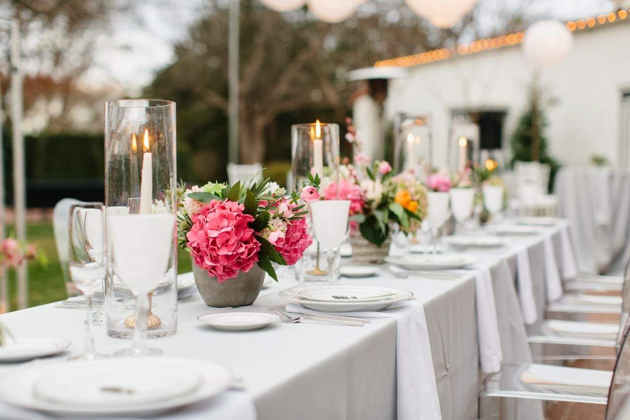 This outside table setup with candles and pink flowers is elegant and beautiful.