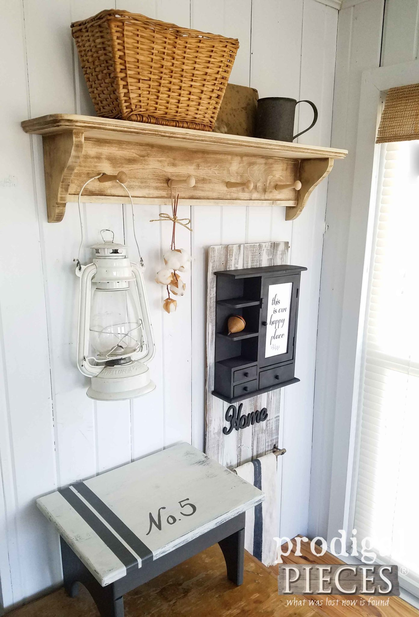 This mud room area with a rustic shelf and hanging lantern is charming.