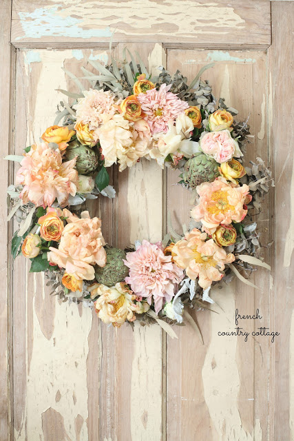This bright flower wreath is charming against the vintage wood door.