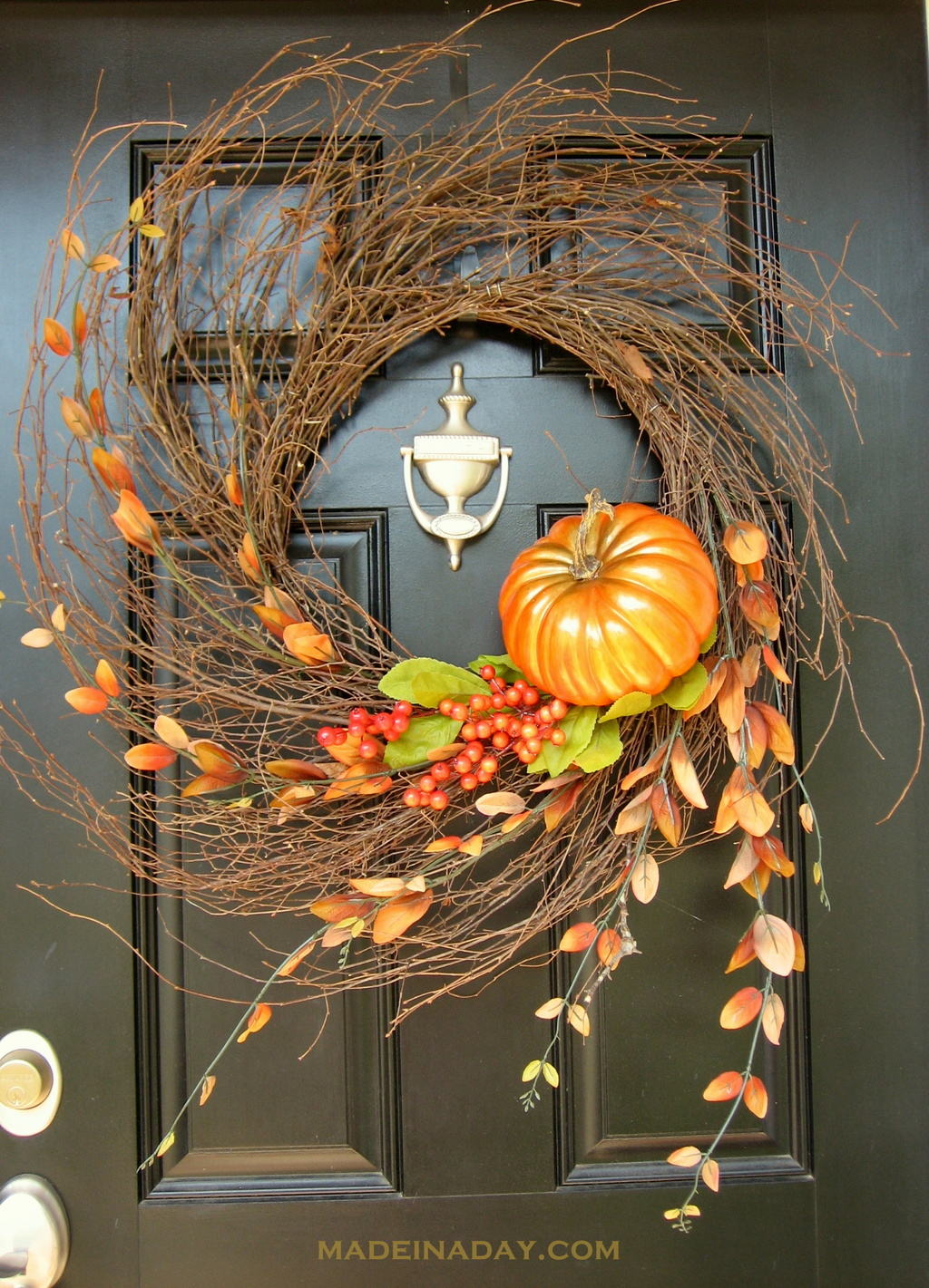 This whimsical fall wreath with a mini pumpkin and leaves is unique.