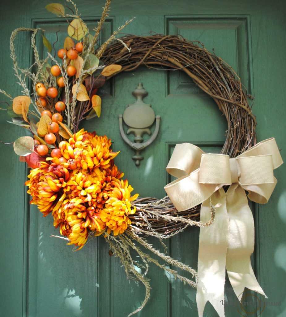 This DIY fall wreath with greenery and a ribbon is festive for fall.