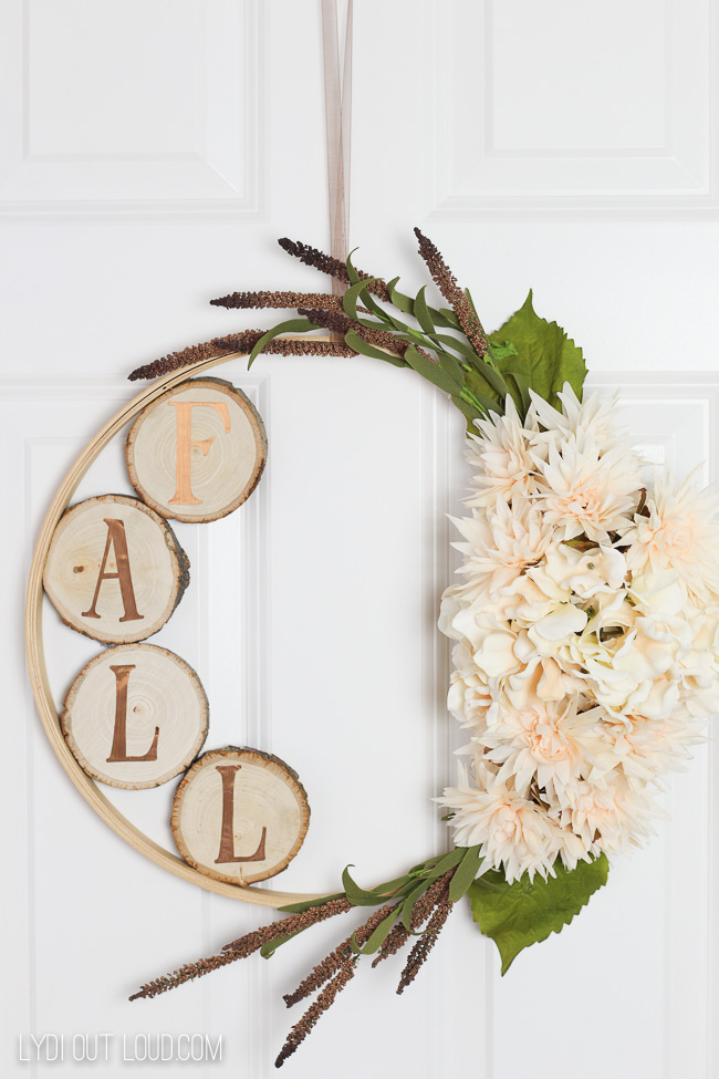 This simple wreath with white flowers and a wood fall sign is simple but cute.
