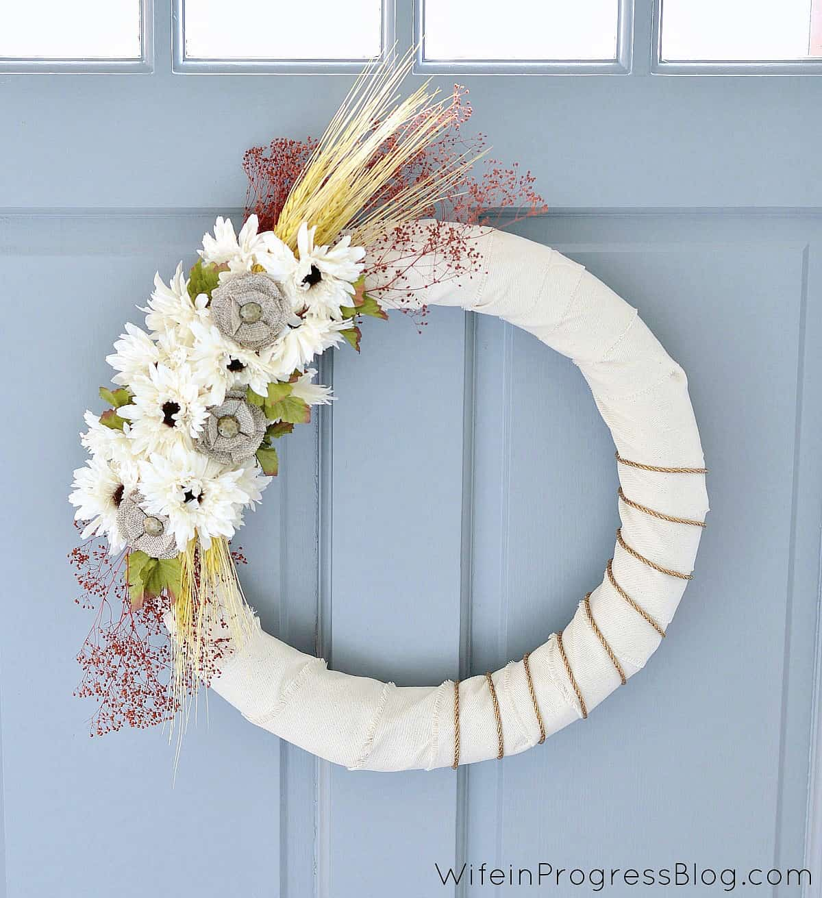 This bright DIY wreath wrapped with ribbon pops against the blue front door.
