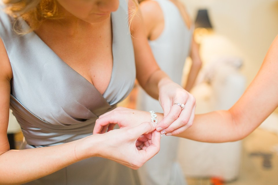 mom putting bracelet on bride