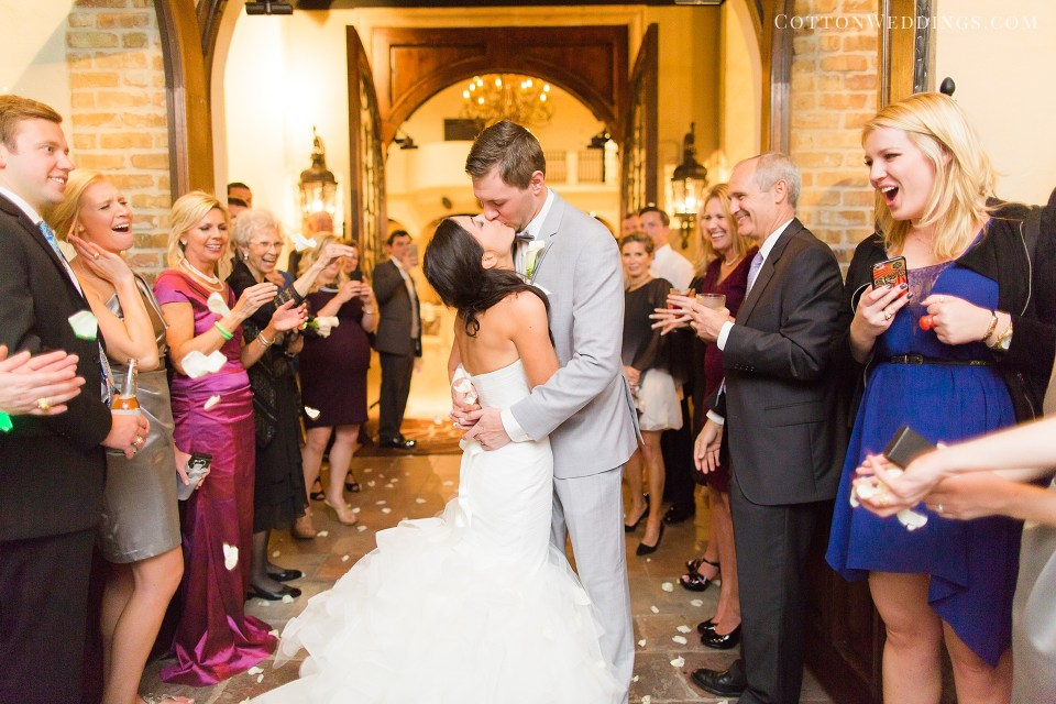 bride and groom kissing with rose petals