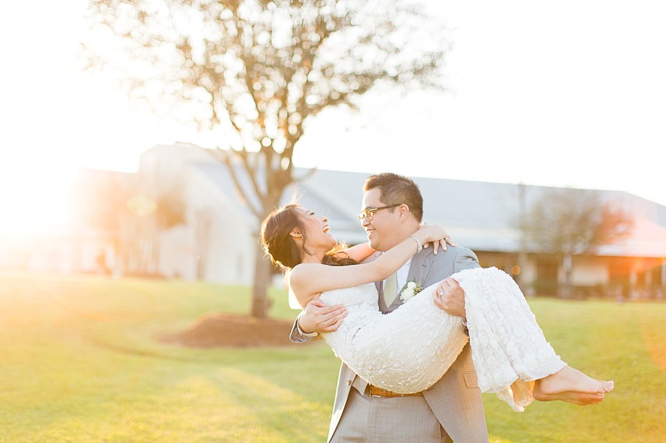 happy groom carrying bride sunset