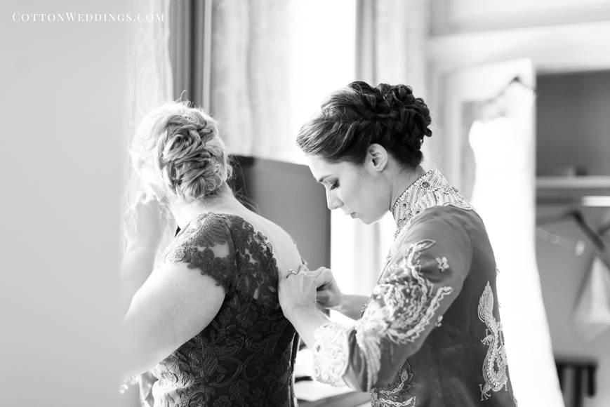 bride helping mother into dress