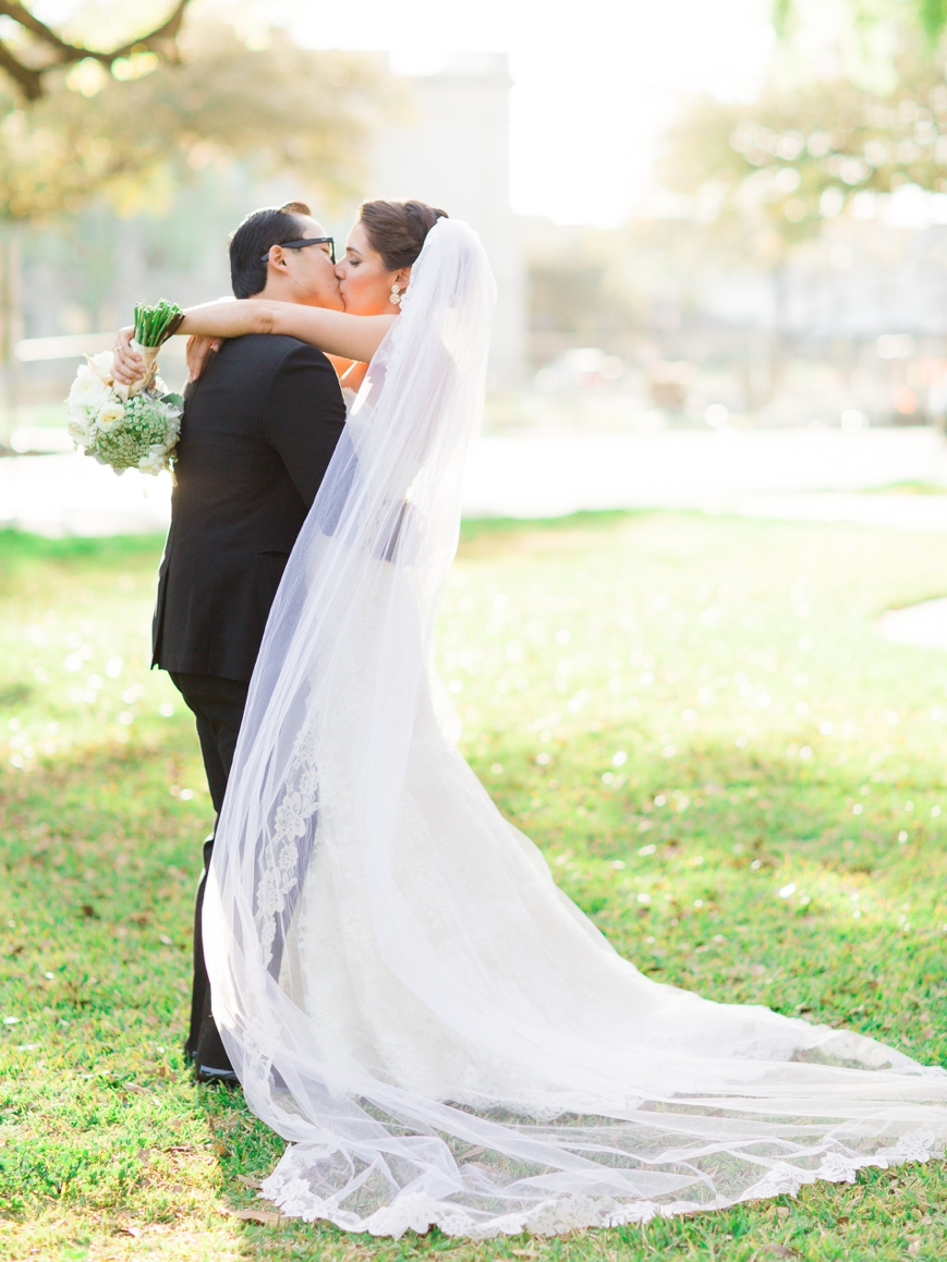 bride and groom kissing with cathedral veil