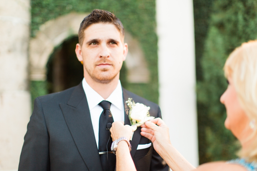mom putting boutonniere on groom