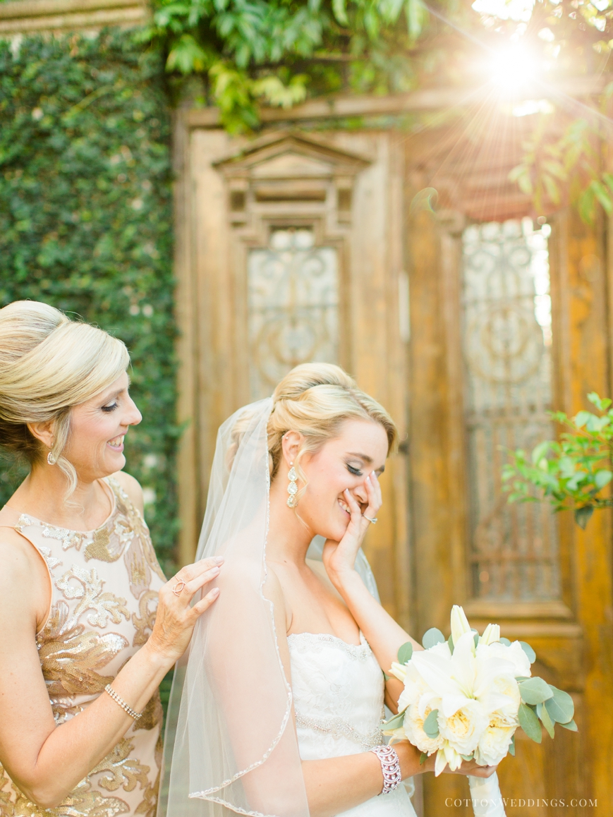 mother of bride putting veil on bride happy