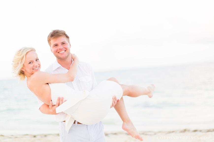 groom holding bride on beach for rehearsal