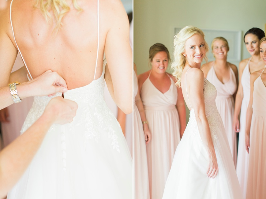 bride putting on dress with bridesmaids