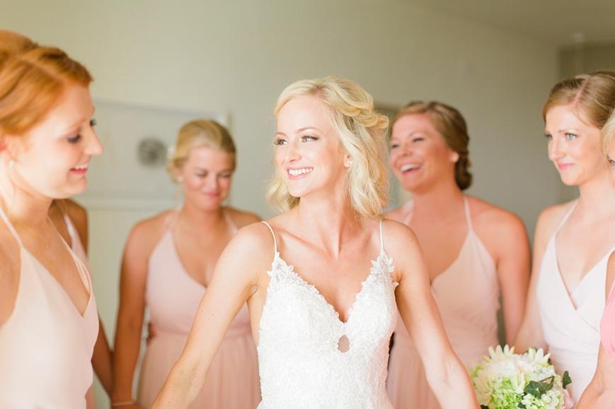 happy bride holding bridesmaids hands