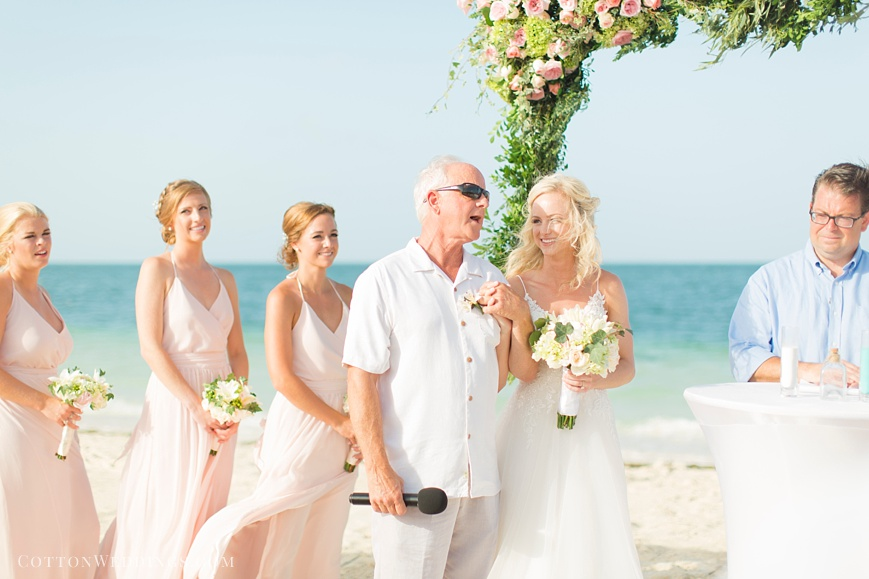 father singing song for bride during beach ceremony