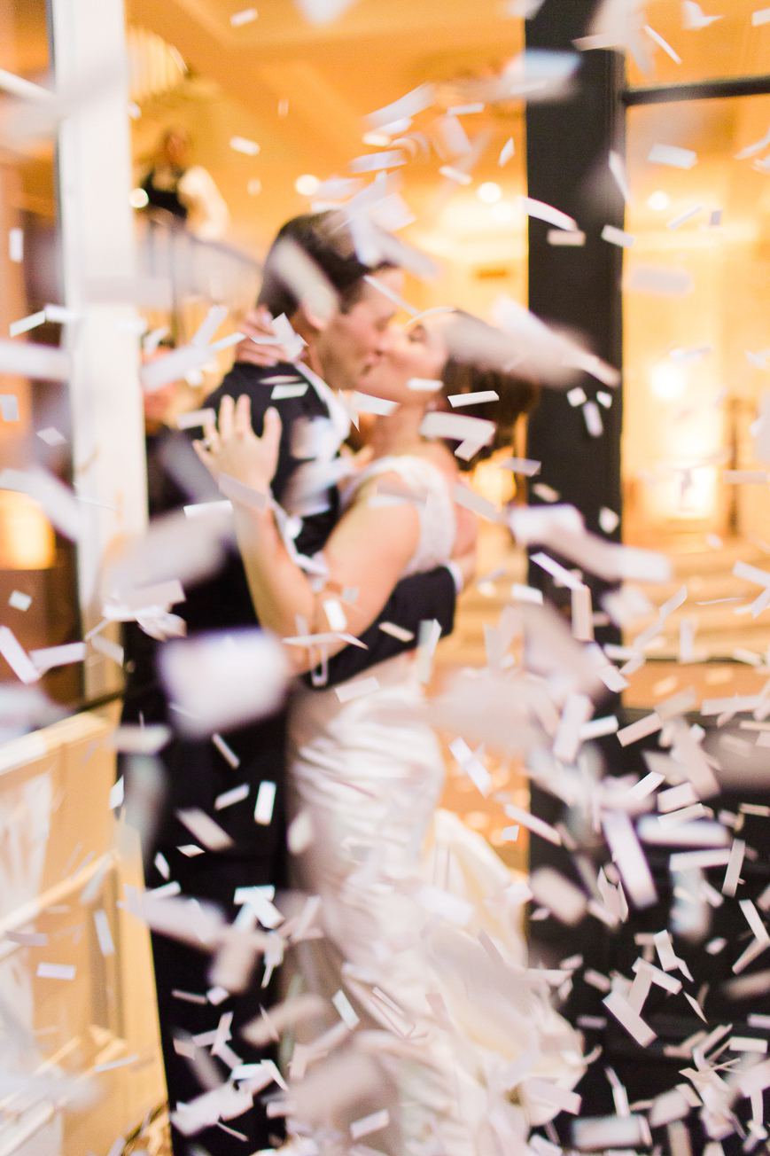 bride and groom kissing confetti exit