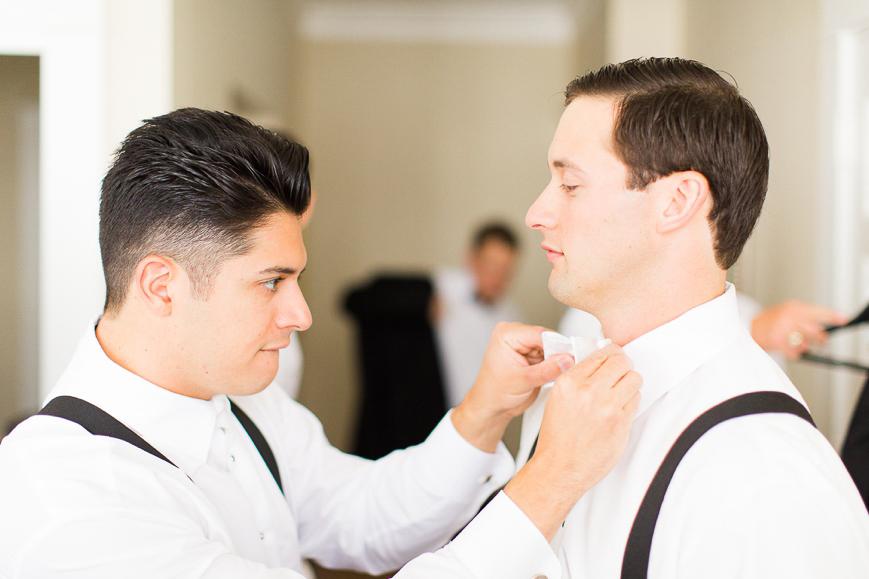 groomsman helping groom with bowtie