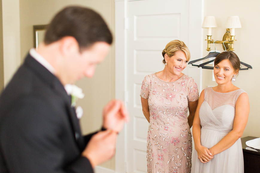 mother and sister of groom watching him open gift