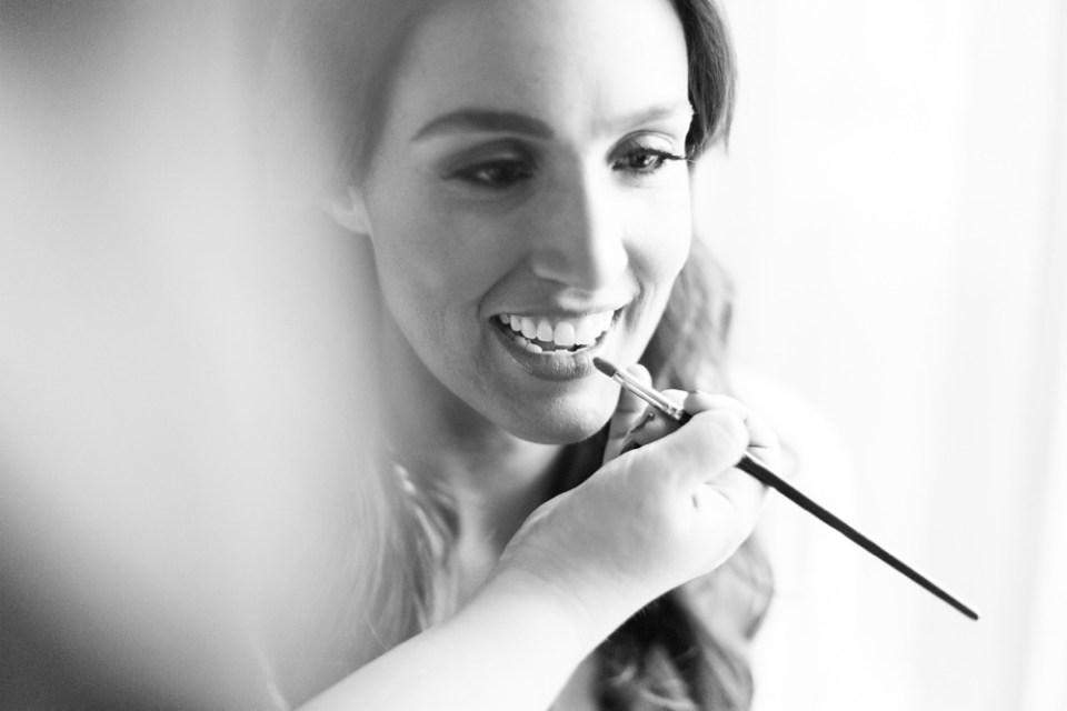 black and white portrait of bride putting on makeup