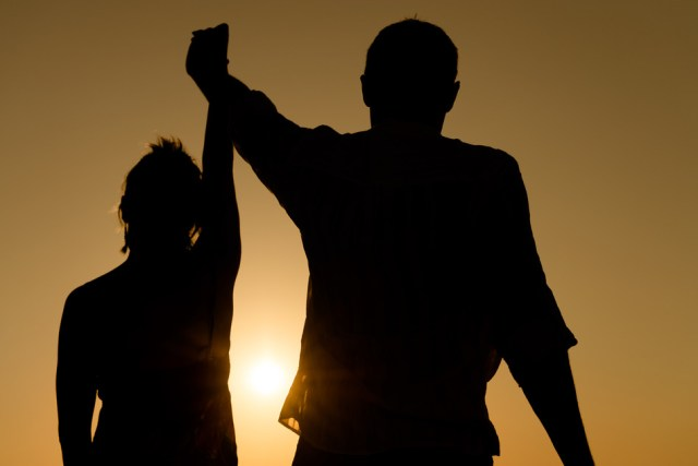 Silhouette of loving couple raise their hands together over orange sunset background