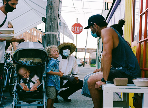 Jide visiting with Cradle NYC customers and their children in the outdoor seating area, Summer 2020.