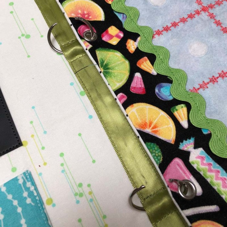 Busy Book made by Julie Cefalu @ The Crafty Quilter.  Showing detail of the book spine, binder rings and page eyelets.