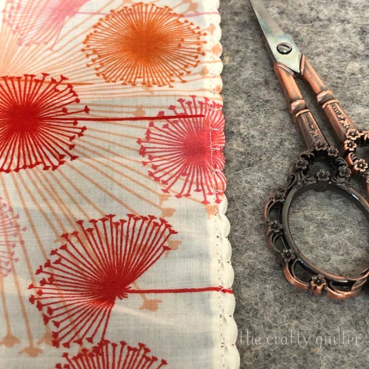 Create a scalloped edge using a blanket stitch or overlock stitch.  Free tutorial for a fabric triangle scarf @ The Crafty Quilter.