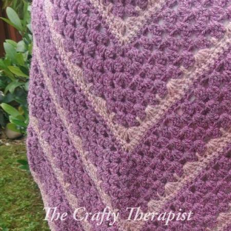 Purple and blush pink crochet shawl made in recycled yarn. Pattern by The Crafty Therapist