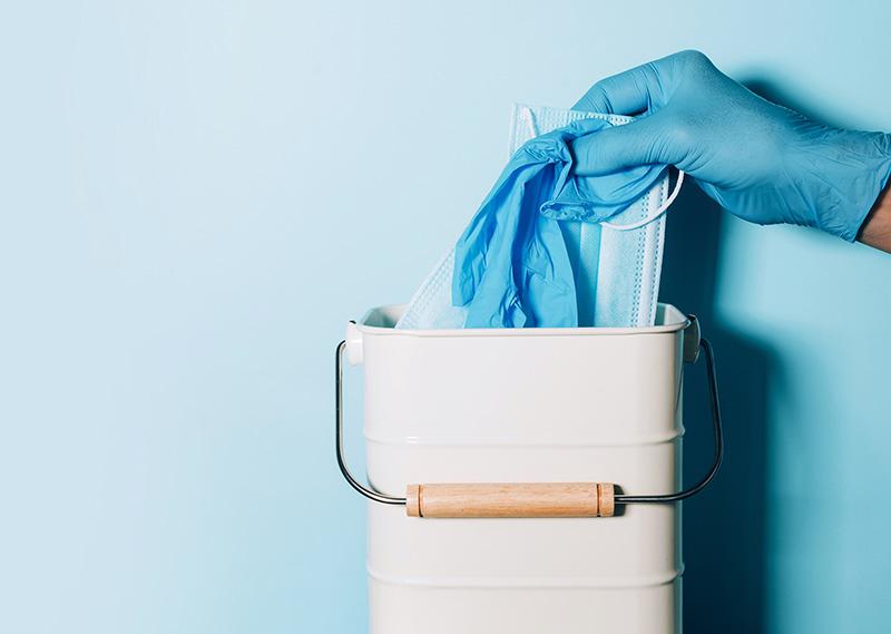 Medical Gloves Hand throwing medical mask in Trash - Crane Center
