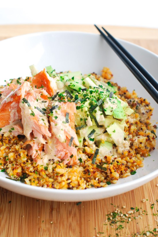 A bowl of quinos and brown rice tossed with flaky smoked salmon, avocado and drizzled with wasabi mayo, served with chopsticks.