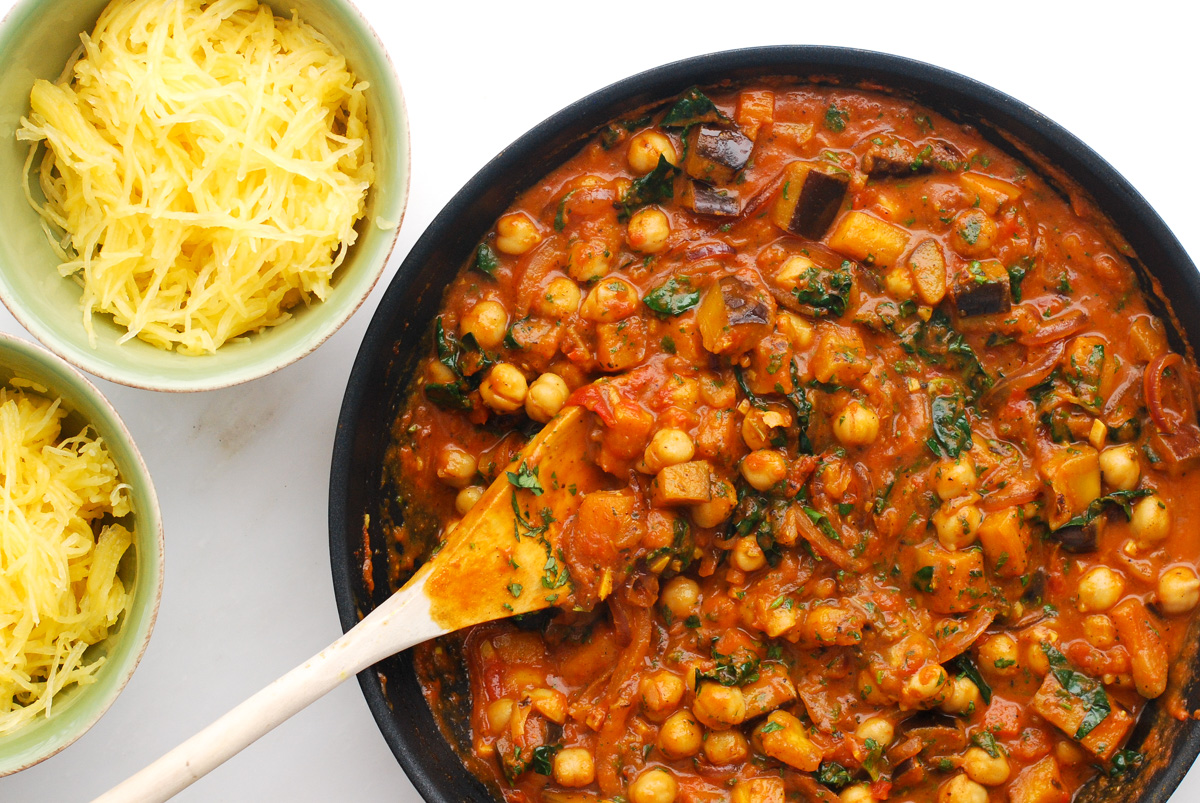 A saute pan of chickpeas, kale and eggplant simmered in a curried tomato sauce with side dishes of spaghetti squash.