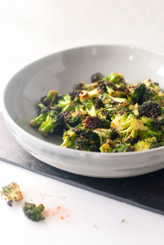 Bowl of charred broccoli sprinkled with paprika.
