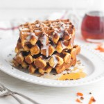 A tower of carrot cake waffles piled high and dripping with yogurt glaze and maple syrup.