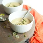 Two bowls of white bean soup topped with pumpkin seeds.