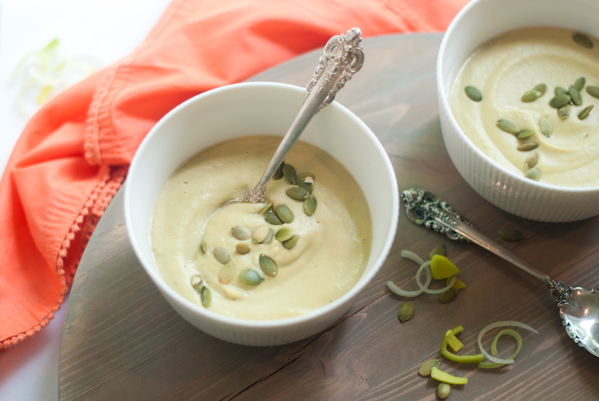 Overhead view of two bowls of white bean soup topped with pumpkin seeds.