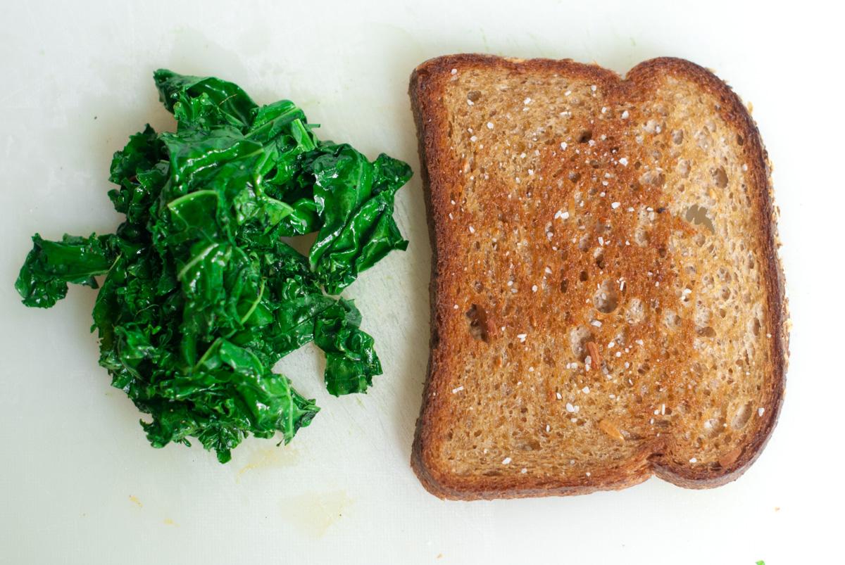 One slice of whole grain toast and a pile of sautéed kale.